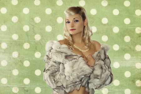Mooi meisje in een zilveren vos bontjas uit poseren op een groene achtergrond Stockfoto