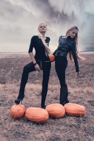 Two sexy girls in a field surrounded by pumpkins on Halloween  photo