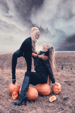 Two sexy girls in a field surrounded by pumpkins on Halloween. photo