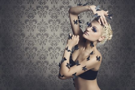 Beautiful girl with black butterflies on the body of fashionable posing against the backdrop of vintage, dramatic wallpaper  photo