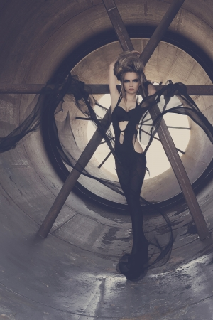 skintight: Young and sexy girl model posing in a tunnel made   of steel, with black skin-tight costumes, featuring high fashion and drama  Stock Photo
