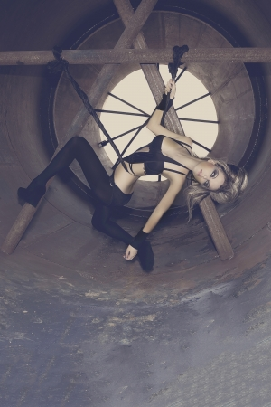 Young and sexy girl model posing in a tunnel made   of steel, with black skin-tight costumes, featuring high fashion and drama  photo