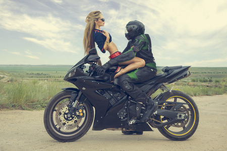 Stylish girl model in seductive outfits, posing in sports motorcycles, desert steppe hills. photo