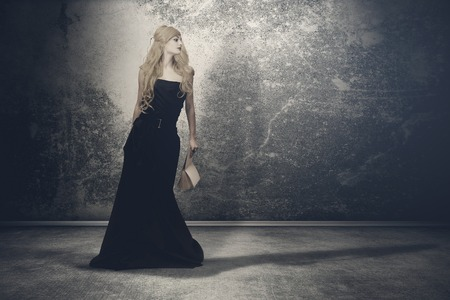 Mysterious woman with long locks in a black gothic dress, standing in the dark and empty room photo