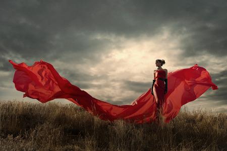 silk fabric: Mujer en vestido rojo ondeando en el viento. Mirando hacia abajo. Foto de archivo