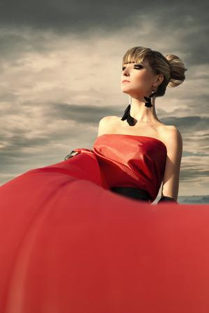 wind down: Woman in red dress waving on wind. Looking down.