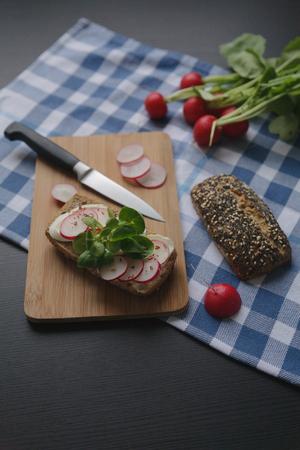 mozarella 치즈와 조각 나무 갈색 커팅 보드에 무 우 샌드위치. 파란색 셀에 원시 야채 늘어서 식탁보. 음식 사진. 스톡 콘텐츠