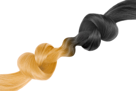 Knots of hair in shape of heart, isolated on white background. Black and blond. Care concept Фото со стока