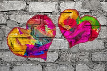 Mehrfarbige Herzen auf grauer Backsteinmauer gemalt