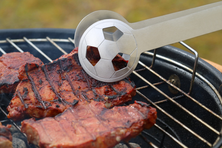 close up of tasty steaks on barbecue grill with Football World Cup tong 스톡 콘텐츠