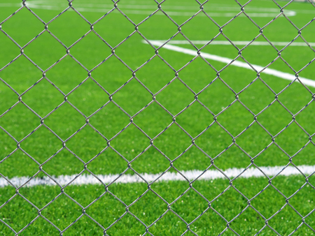 close up of football field behind chain link fence