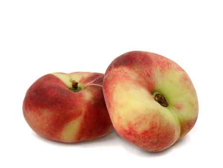 Prunus Persica, two flat peaches isolated on a white background Stockfoto