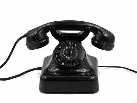 front view of old vintage black rotary dial telephone isolated on white background, retro bakelite phone
