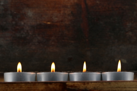 four tealights, candles on dark wooden background Standard-Bild
