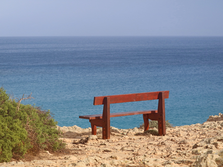 single bench in the park Cavo Greco in Ayia Napa, cyprus overlooking the mediterranean Sea