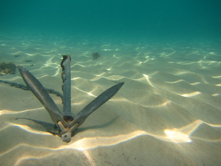 Underwater background with anchor on sandy bottom