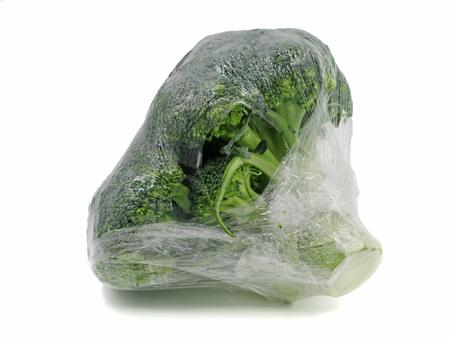 Brokkoli in Plastikfolie eingewickelt isoliert auf weißem Hintergrund Standard-Bild
