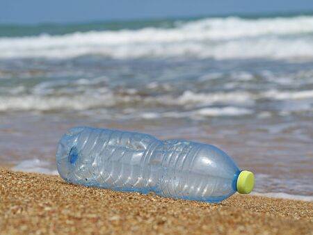 plastic bottle in the sand on beach with waves in the background, concept of sea pollution with plastic waste