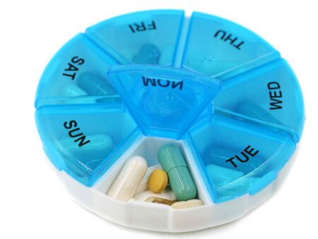 close up of round pill box with Mondays pills visible on white background