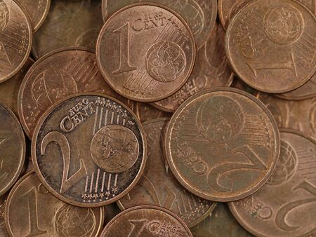 close up of old used one and two euro cent coins background, end of small change or cash