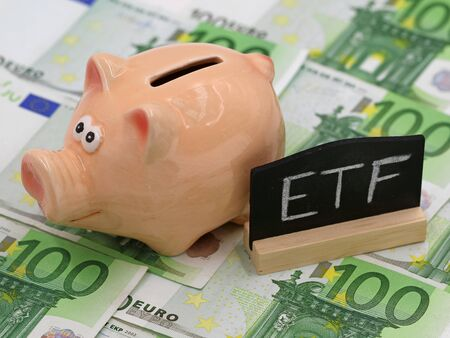Piggy bank and blackboard which shows ETF on hundred euro banknotes