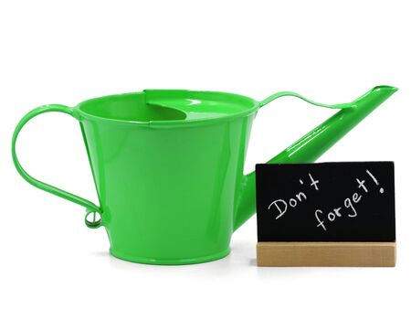 green watering can with mini blackboard isolated on white background, concept of dont forget watering Archivio Fotografico