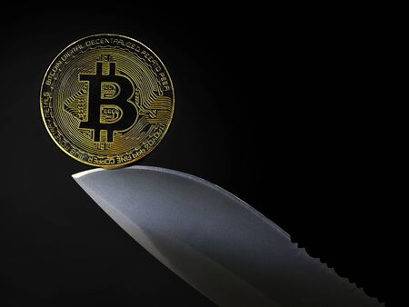 golden bitcoin coin on knife blade isolated on black background with copy space