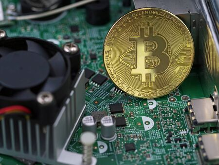 Bitcoin golden coin on computer motherboard between microchips and processor, concept of virtual cryptocurrency