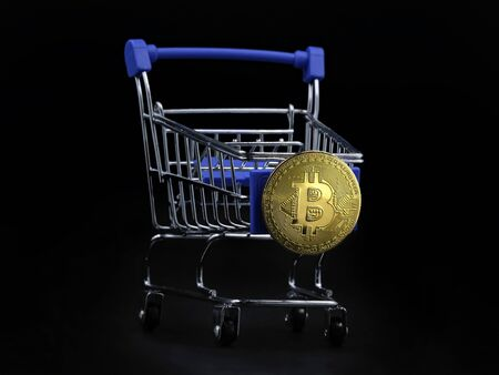 Shopping cart with gold bitcoin on the front isolated on black background