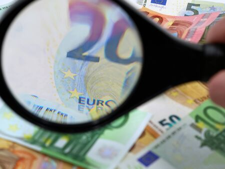 magnifying glass inlarge 20 euro on pile of banknotes Archivio Fotografico