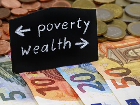 poverty and wealth shows the way on a blackboard on euro banknotes, divided society between poor and rich