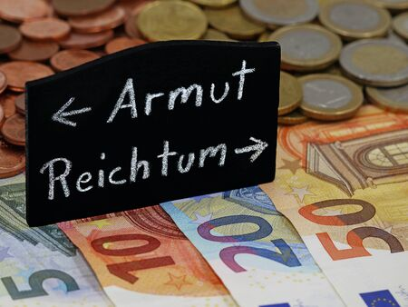 german word for poverty and wealth shows the way on a blackboard on euro banknotes, divided society between poor and rich Archivio Fotografico