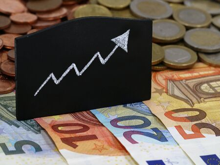growing arrow on blackboard with euro banknotes and coins