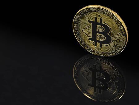 golden bitcoin on black background with reflection and copy space