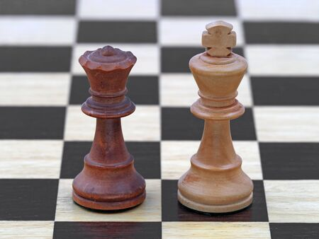Chess black queen and white king stand on a wooden chessboard