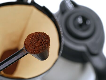 spoon with coffee powder in front of coffee strainer with coffee pot on background. concept of making coffee