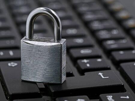 silver padlock on black computer keyboard, close up