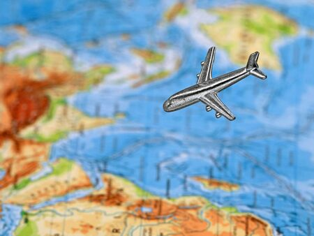 silver miniature airplane above blurred map on background
