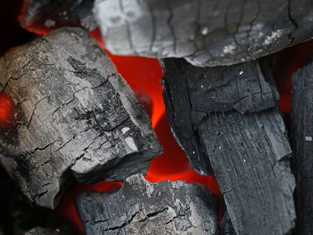 close up of glowing coals in a barbecue grill, charcoal background