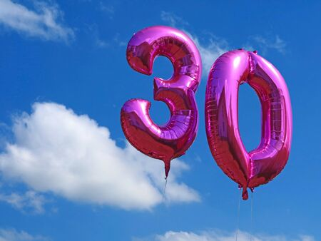 pink helium balloons on blue cloudy sky, celebrating the age thirty with number balloons, birthday background