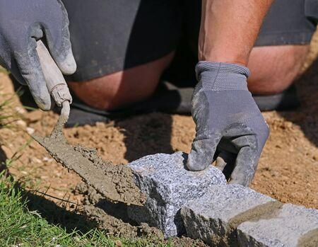 Close up photo of worker with trowel and gloves, laying a lawn edge massive granite blocks as a part of garden limitation. Detail of bricklayers working hands using mortar