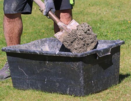 Concrete mortar mixed in black bucket with spade by worker in garden, close up Archivio Fotografico