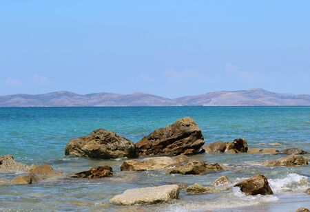 stone rocks on coast in clear blue water with blue sky and mainland at horizon, view from kos, greece to turkey Archivio Fotografico