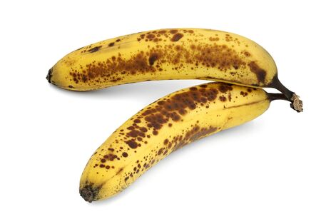 two brown spotted, overripe bananas on white background