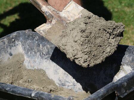 Concrete mortar mixed in black bucket with spade by worker in garden, close up. Archivio Fotografico