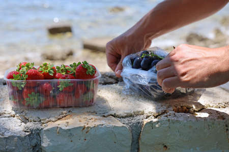 Juicy and ripe fruits on stone wall in front of the sea, healthy nutrition on beach
