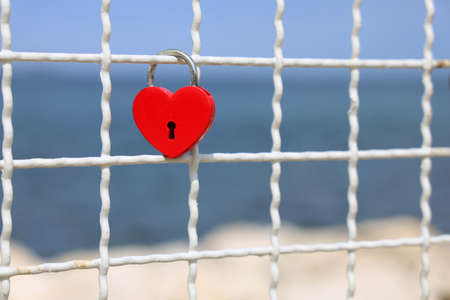 Red heart padlock on fence in front of blue sea Archivio Fotografico