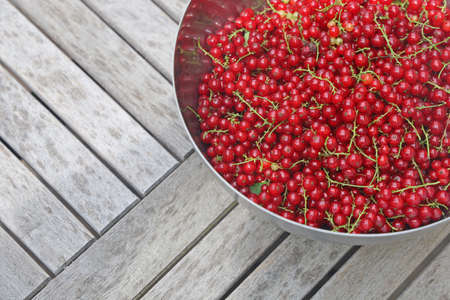 bowl of fresh harvested red currant berries on wooden table with copy space Archivio Fotografico