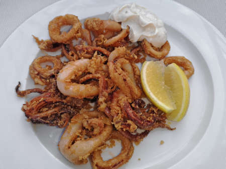 Fried calamari rings with sauce and lemon, delicious squids, octopus