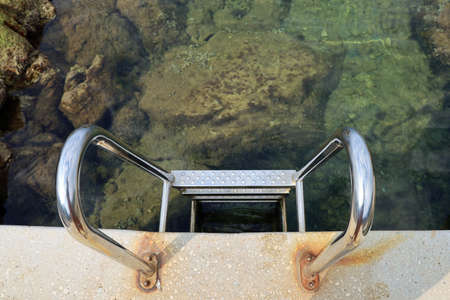 top view of a metal stairs leading into the sea water